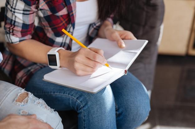 Tomando notas. close de um lápis sendo segurado por uma mulher simpática e agradável e sendo usado para escrever enquanto toma notas Foto Premium