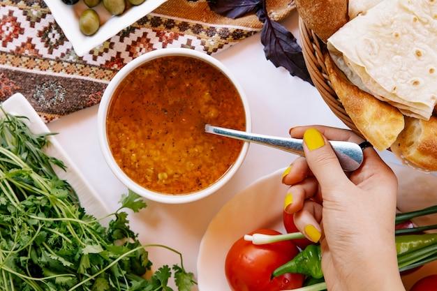 Tomando sopa de beterraba russa com uma colher. Foto gratuita