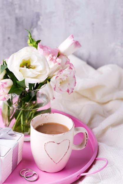 Tomar uma xícara de café com chocolate, flores eustoma e caixa de presente na bandeja no cobertor na cama. Foto Premium