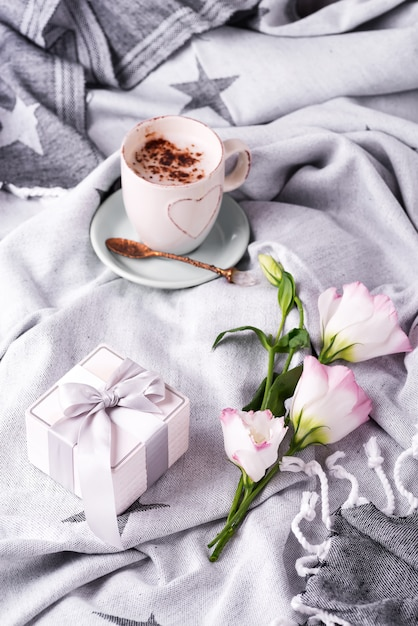 Tomar uma xícara de café com chocolate, flores eustoma e caixa de presente no cobertor na cama. Foto Premium