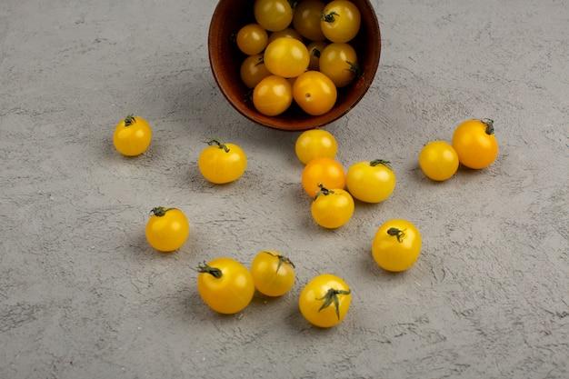 Tomate amarelo maduro fresco dentro e fora do pote redondo marrom no cinza Foto gratuita