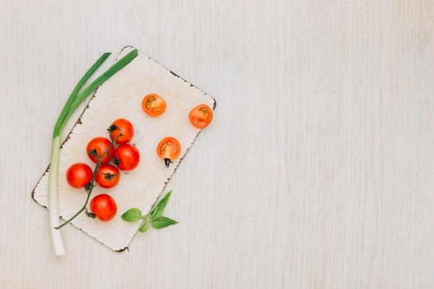 Tomate cereja; alho-porro e folhas na tábua sobre a mesa Foto gratuita