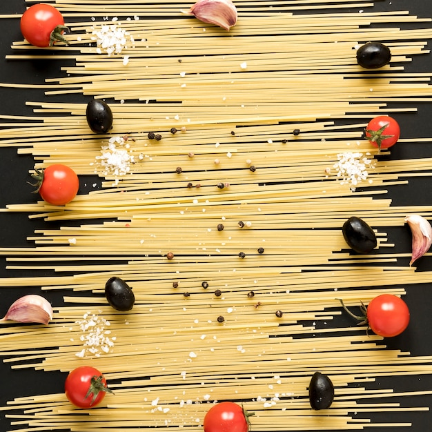 Tomate cereja; azeitonas pretas; dentes de alho; blackpepper dispostos em espaguete cru Foto gratuita
