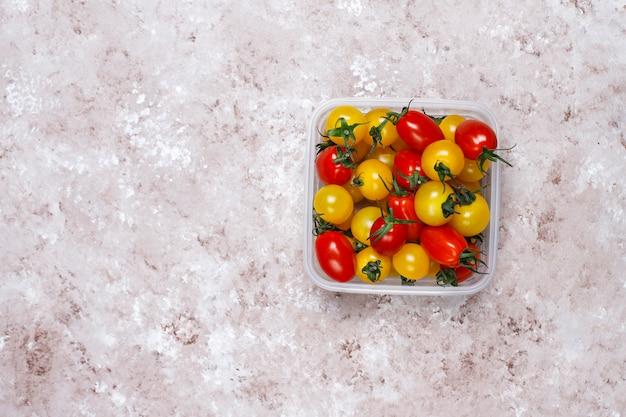 Tomate cereja de várias cores, tomate cereja amarelo e vermelho sobre fundo claro Foto gratuita