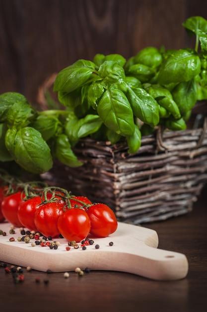 Tomate cereja e ervas verdes frescas na madeira Foto gratuita