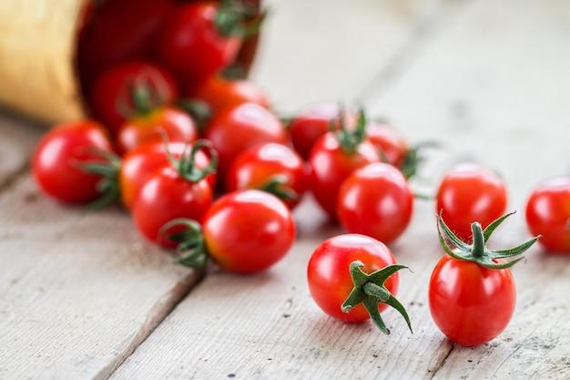 Tomate cereja vermelho pequeno derramamento de uma cesta de vime Foto Premium