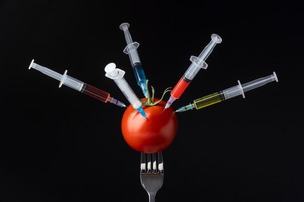 Tomate cheio de seringas Foto gratuita