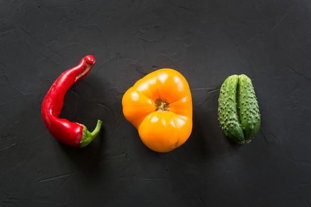 Tomate colorido orgânico feio, pimenta, pepino no preto. Foto Premium