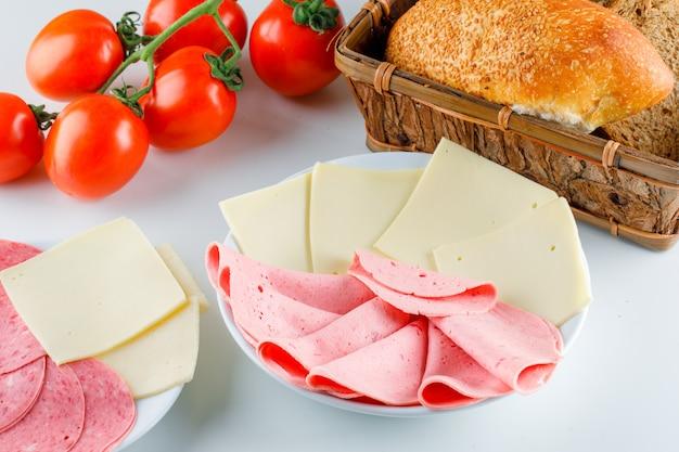 Tomate com pão, queijo, salsicha, vista de alto ângulo Foto gratuita
