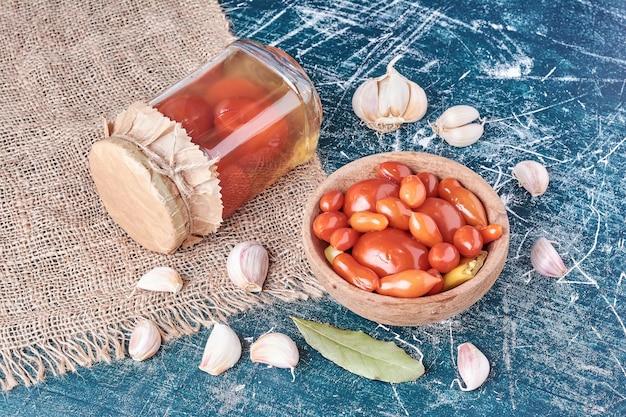 Tomate em conserva em frasco de vidro e tigela com alho no azul. Foto gratuita