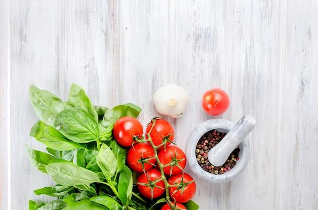 Tomate, manjericão verde e especiarias em um almofariz de pedra Foto Premium