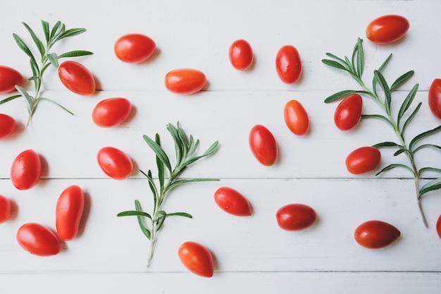 Tomates de alecrim são colocados em uma mesa branca. Foto Premium
