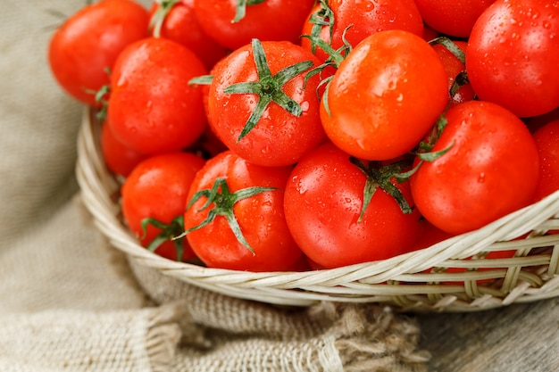Tomates de cereja maduros e suculentos com gotas da umidade em uma cesta de vime. mesa de madeira velha, em torno da tela de serapilheira Foto Premium