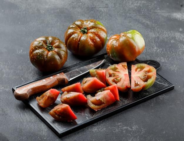 Tomates kumato fatiados com faca na parede cinza e placa de corte. Foto gratuita
