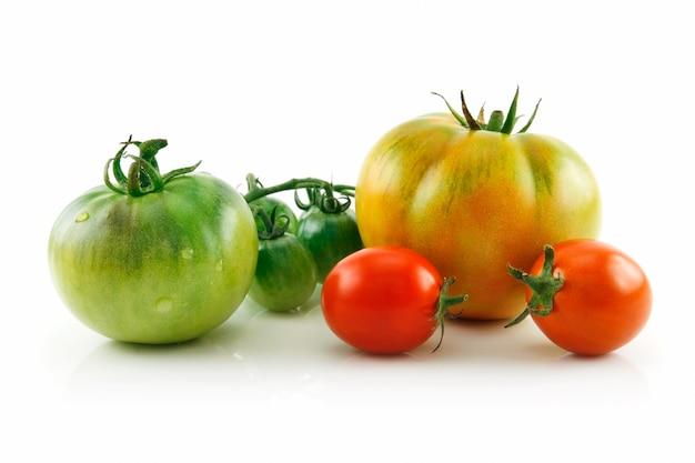 Tomates vermelhos e amarelos molhados maduros isolados no fundo branco Foto Premium