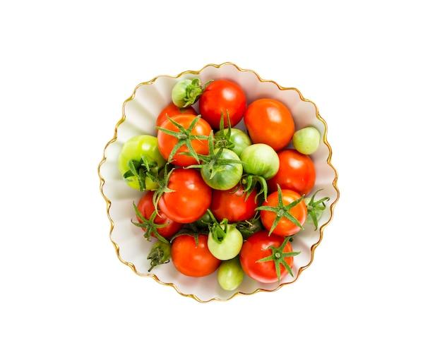 Tomates vermelhos e verdes pequenos na bacia branca. Foto Premium