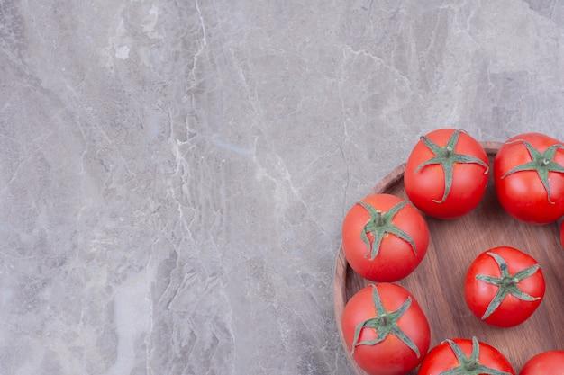 Tomates vermelhos em uma bandeja de madeira no mármore. Foto gratuita