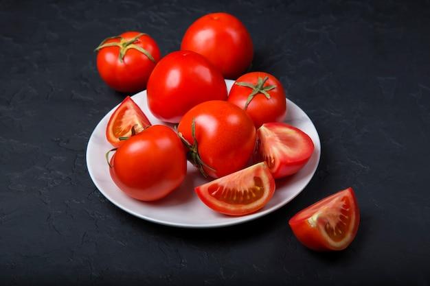 Tomates vermelhos frescos em um prato branco. close-up, copie o espaço. Foto Premium