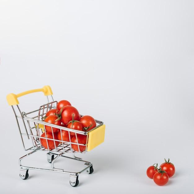 Tomates vermelhos frescos no carrinho no fundo branco Foto gratuita