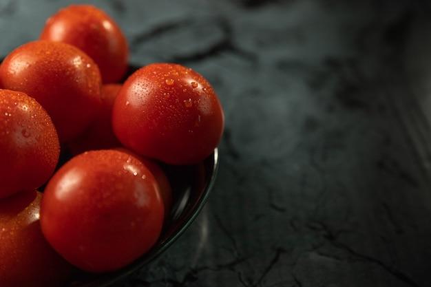 Tomates vermelhos grandes em uma placa preta, em uma mesa de granito Foto Premium