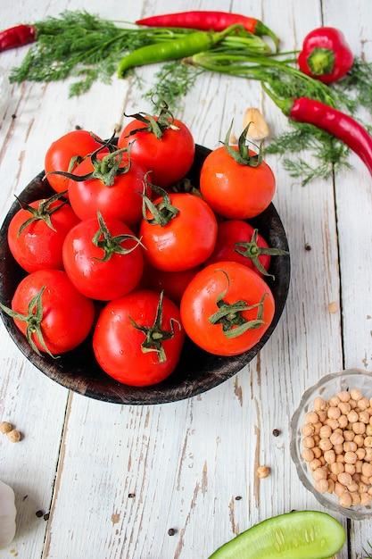 Tomates vermelhos orgânicos frescos em chapa preta na mesa de madeira branca com verde e vermelho e pimenta, pimentão verde, pimenta preta, sal, close-up, conceito saudável Foto gratuita