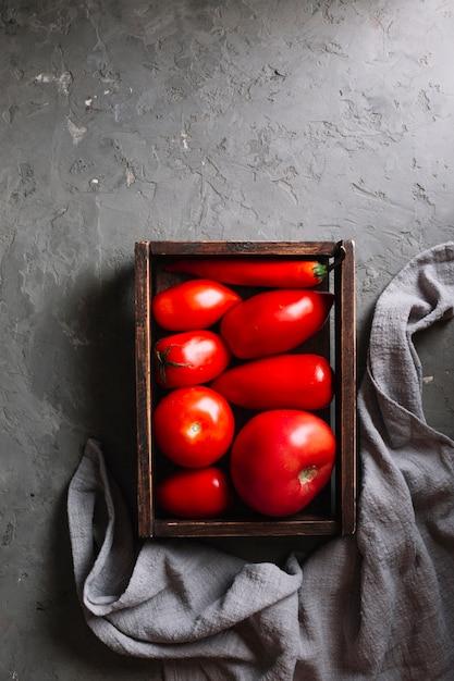 Tomates vermelhos saborosos em uma cesta plana leigos Foto gratuita