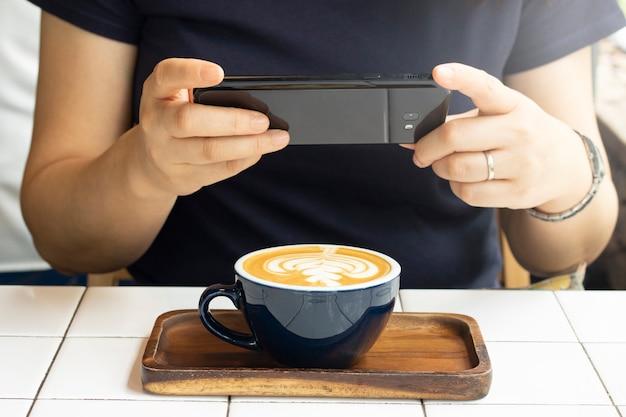 Tome café com leite de foto em um copo com telefone celular Foto Premium