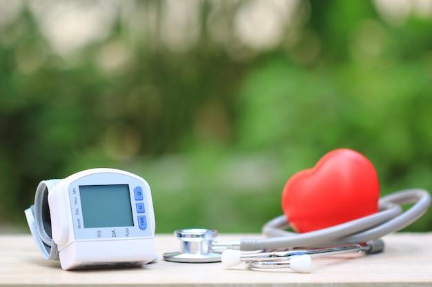 Tonômetro médico para medir a pressão arterial com estetoscópio e coração vermelho sobre fundo verde, conceito de cuidados de saúde Foto Premium