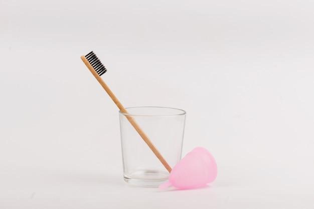 Toothbrush de bambu e copo menstrual no vidro no fundo branco. desperdício zero Foto Premium
