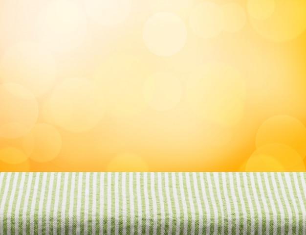 Top de pano vazio de mesa verde em fundo laranja bokeh luz Foto Premium