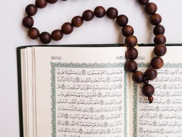 Top shot close-up abriu o alcorão com contas de oração Foto gratuita