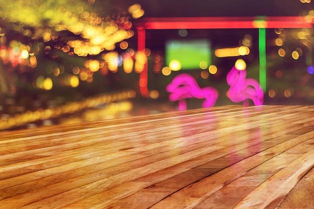 Topo da mesa de madeira vazia com luz de borrão de fundo de boate Foto Premium