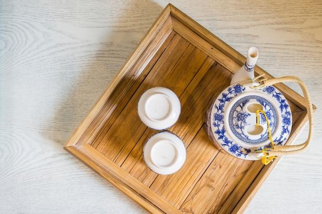 Topo da tradicional xícara branca de chá e bule em closeup de bandeja de madeira na mesa Foto Premium