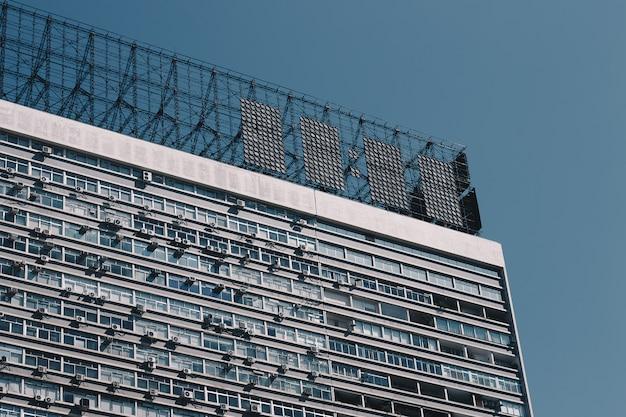 Topo de um antigo prédio de apartamentos com projéteis de metal no telhado e céu azul claro Foto gratuita