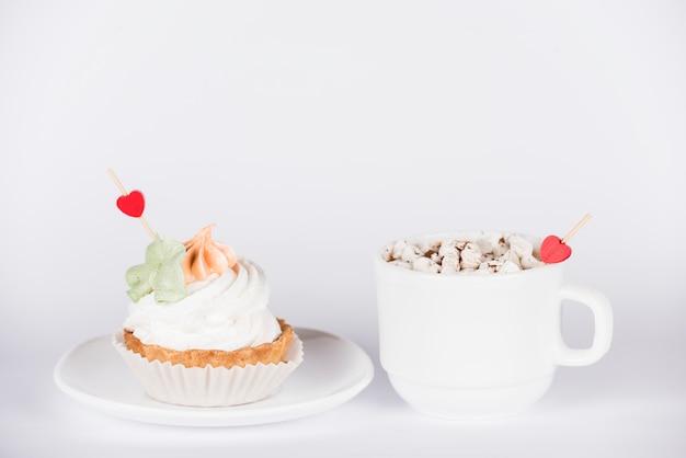 Toppers de coração no cupcake e xícara de café Foto gratuita
