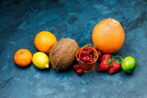 Toranja com laranja, limão, limão, morango, cereja, tangerina, coco deitado sobre uma superfície azul suja Foto gratuita