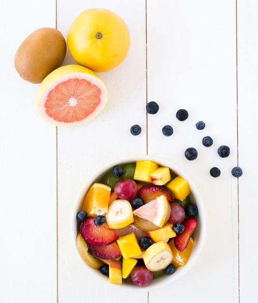 Toranja; kiwi e mirtilos com tigela de salada de frutas na mesa de madeira branca Foto gratuita