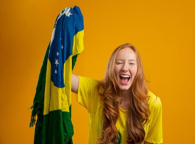 Torcedor do brasil. fã de mulher ruiva brasileira comemorando no futebol, jogo de futebol, cores do brasil. vestindo uma camiseta, bandeira e chapéu de fã. Foto Premium