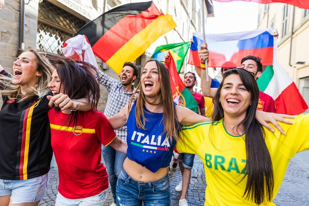 Torcedores felizes fãs de diferentes países caminhando e cantando juntos Foto Premium