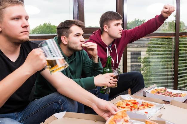 Torcedores masculinos assistindo futebol na tv e bebendo cerveja. três homens bebendo cerveja e se divertindo juntos no bar Foto gratuita