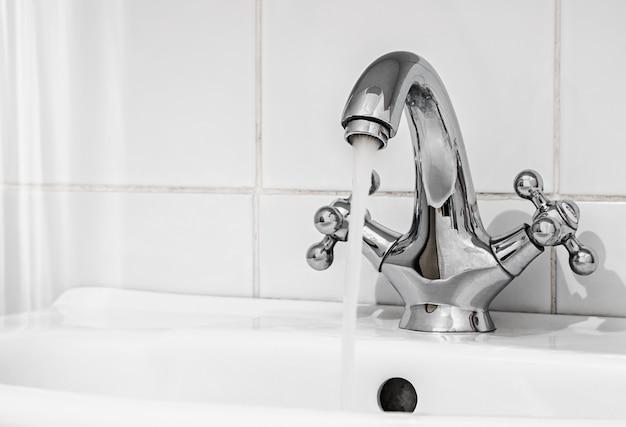 Torneira de água com um fluxo de água no banheiro Foto Premium