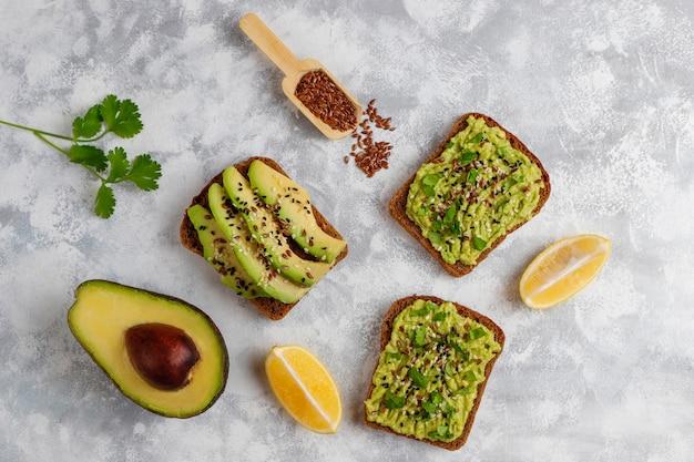 Torrada de abacate com fatias de abacate, limão, sementes de linho, sementes de gergelim, fatias de pão preto, vista superior Foto gratuita