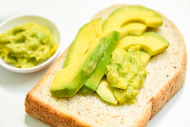 Torrada de abacate e torrada de abacate no conceito de comida saudável de frutas de fundo de chapa branca Foto Premium