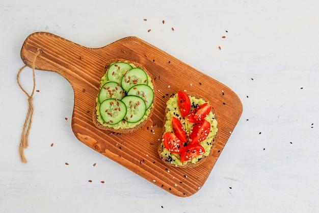 Torrada de abacate em pão integral com legumes, tomates amarelos e vermelhos Foto gratuita