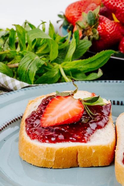 Torrada de morango de lado vista pão branco com geléia de morango e hortelã em cima da mesa Foto gratuita