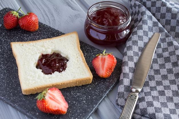 Torrada de pão com geleia de morango na tábua cinza Foto Premium