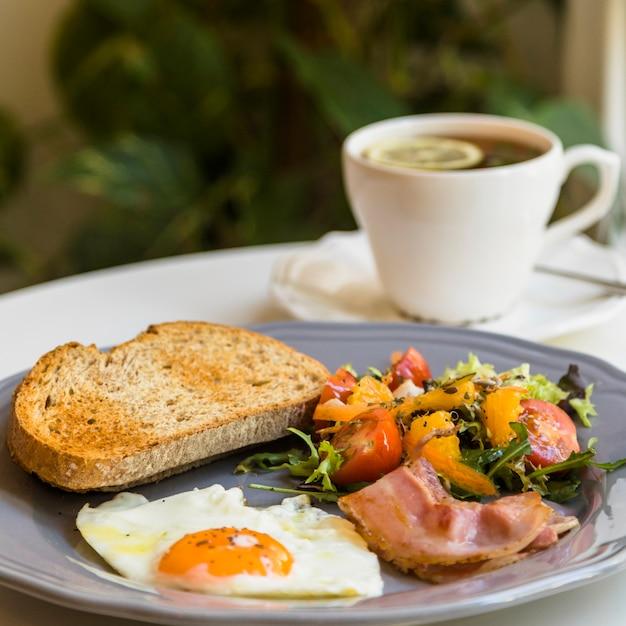Torrada; meio ovo frito; salada e bacon na placa cinza perto da xícara de chá Foto gratuita