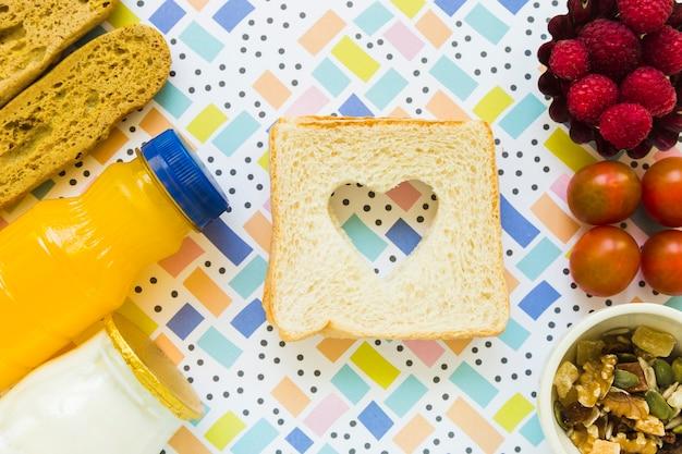 Torradas com coração perto de comida saudável Foto gratuita