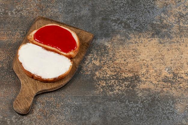 Torradas com geléia e creme de leite na tábua de madeira. Foto gratuita