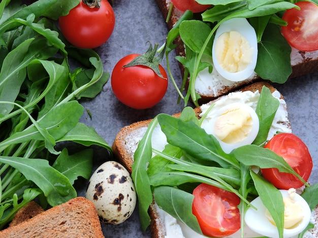 Torradas de centeio com rúcula, ovos de codorna e tomate cereja. Foto Premium